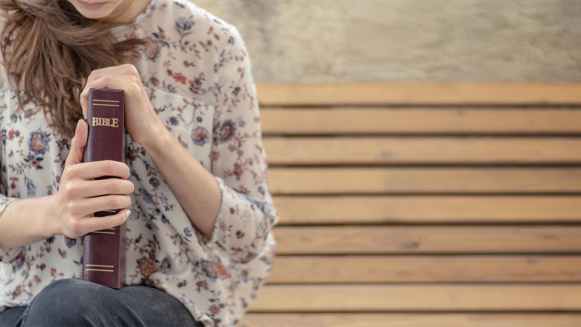 Foto di una ragazza seduta con la Bibbia tra le mani