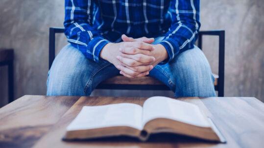Foto di un uomo che prega on la Bibbia sul tavolo