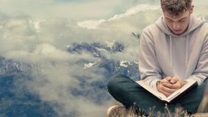 Foto di un Giovane che legge la Bibbia seduto a terra