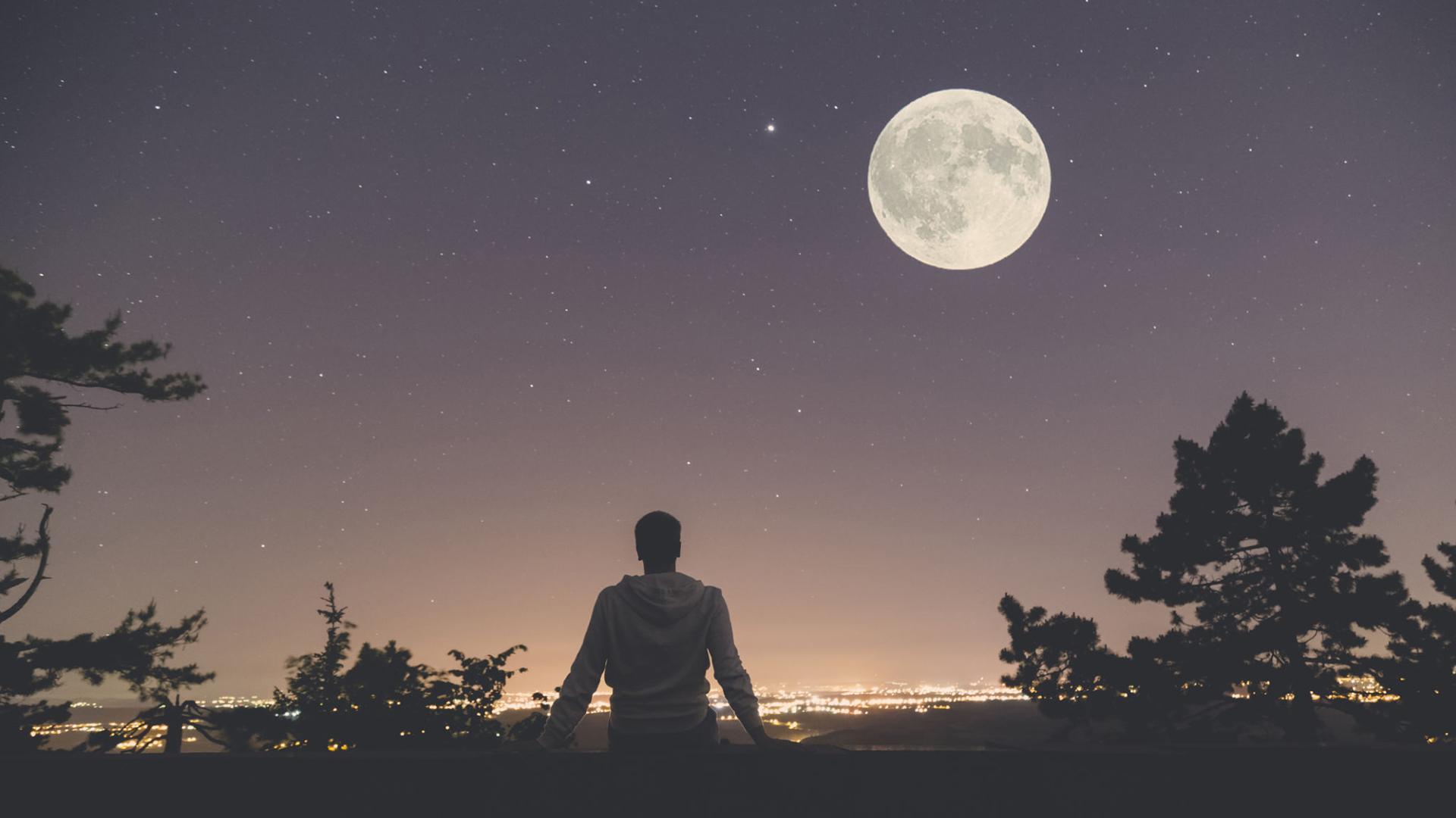 Foto di un ragazzo seduto a terra a guardare la luna