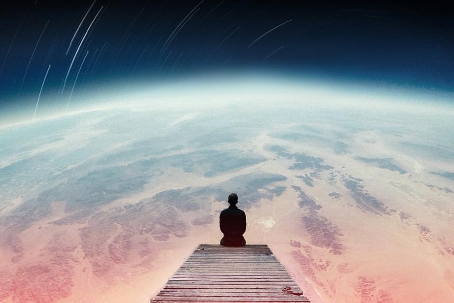 Uomo seduto nello spazio che osserva il mondo