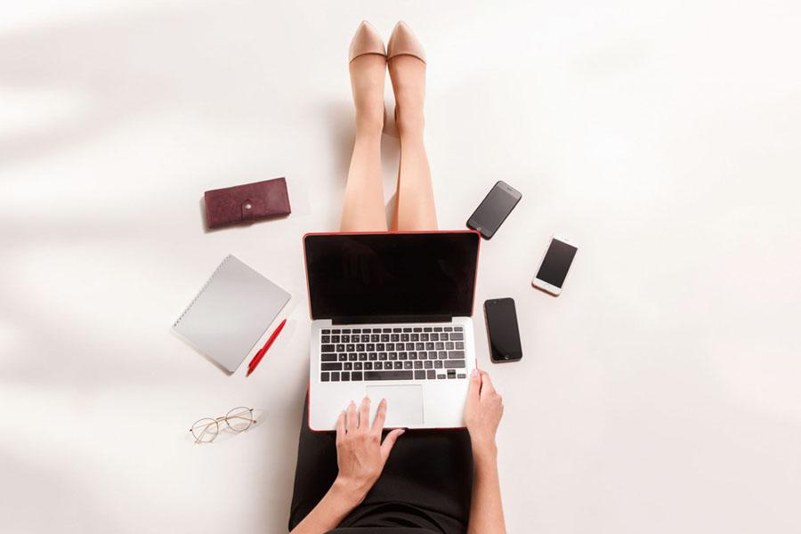 Computer poggiato sulle gambe di una ragazza